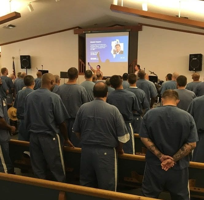 A group of inmates gather to watch and discuss GLS19.